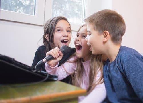 three kids singing karaoke together